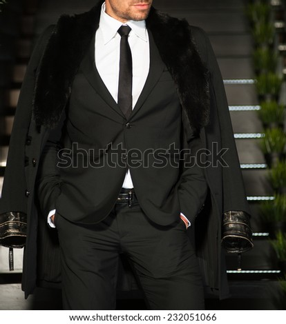 man in a black suit and overcoat. - stock photo