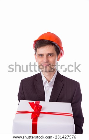 man in a helmet in a suit gives a gift white gift box with red ribbon bow, isolated over white background. - stock photo