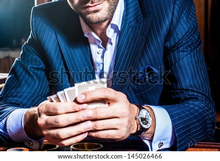 man in a suit  player sits with cards in a hand - stock photo