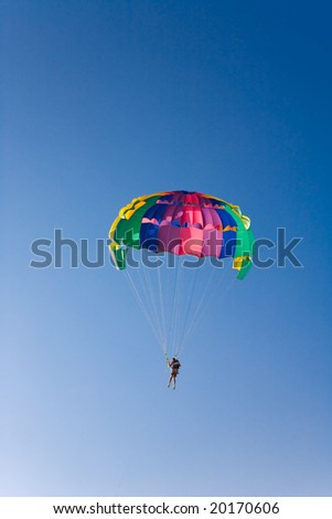 Man is parasailing in the blue sky - stock photo