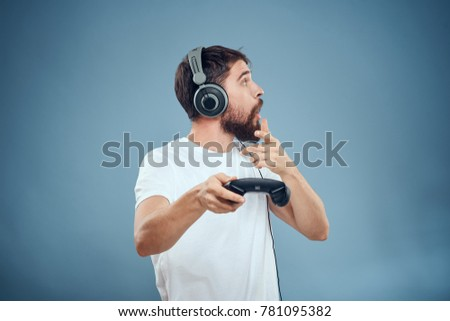 man listening to music with headphones playing in playstation on a blue background