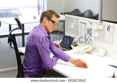 man  office worker,exercising during work with tablet in his office - stock photo