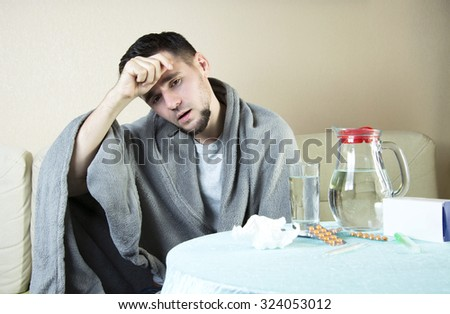 man On Sofa With Medicine And Glass Of Water Man  having flu takes pills, checking fever . flu, colds, fever - seasonal disease - stock photo
