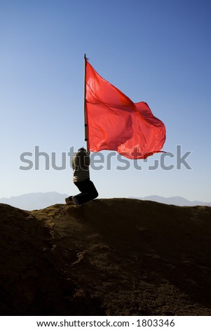 man pushing a red flag into the ground - stock photo