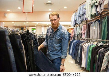 Man selecting new clothes in   store.
