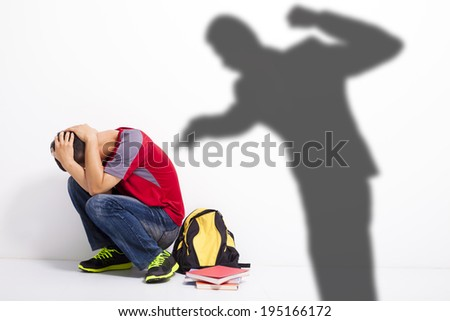 Man shadow attack   to terrified student with a fist  - stock photo