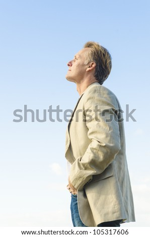 man standing in profile	wearing a beige colored jacket and white t'shirt