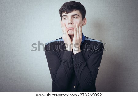 Man thinking about something, shock, surprise, bad teeth hurt, sadness, dreams, tired. On a gray background. - stock photo