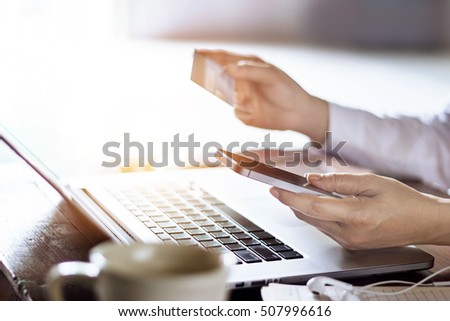 Man using mobile payments with credit card for online shopping on laptop background, m-banking