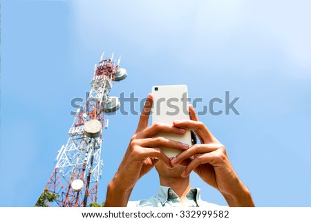 Man using smart phone devices with Telecommunication tower  blue sky background - stock photo