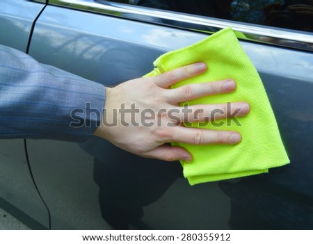 man washing a car with a rag - stock photo