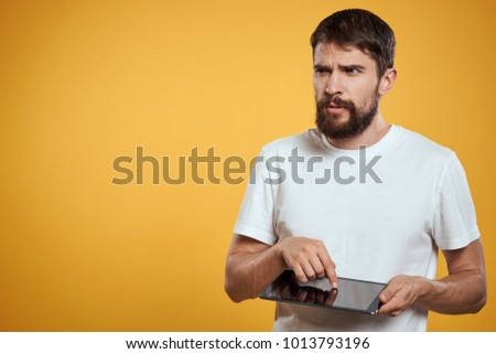 man with a beard holding a tablet looking away on a yellow background