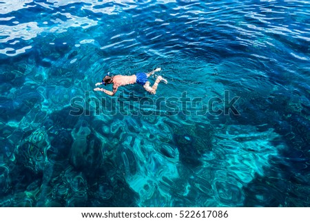 man with scuba mask floats in the sea turquoise clear water