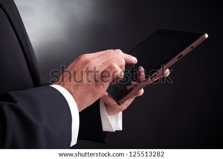 Man working with a tablet computer on black background - stock photo