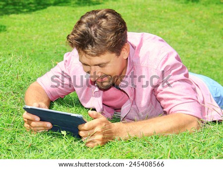 man working with tablet computer outdoor in park - stock photo