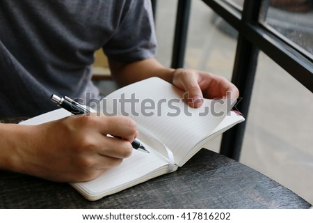 man write pen on notebook near window ,hand writing pen on paper page,hardworking for achievement business target concept, write idea by pen. - stock photo