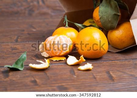 mandarin orange pouring out of  vintage paper sack. - stock photo