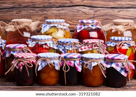 Many glass jars with conservation. Storing of canned foods. - stock photo
