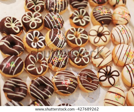 Many small donuts flavors like strawberry, berries, milk chocolate . And stuffed with fruit paste together .