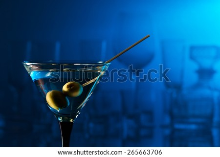martini with green olives on a blue background - stock photo