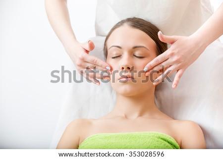 masseur makes massage of the face brunette - stock photo