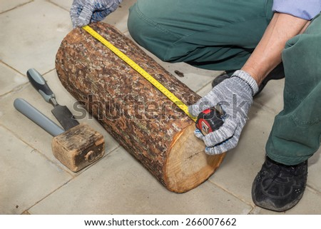 Master measures the length billet of logs on floor - stock photo