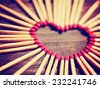 matchsticks in the shape of a heart toned with a warm retro vintage instagram filter effect - stock photo