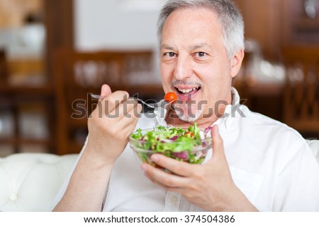 Mature man eating a healthy salad