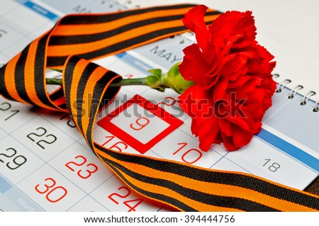 9 May card - bright red carnation wrapped with George ribbon lying on the calendar with framed 9th May date. 9 May concept.   - stock photo