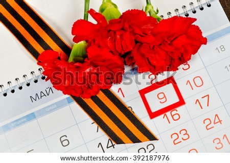 9 May concept. Postcard for Victory Day in Great Patriotic War in Russia- St George ribbon and red carnations over the calendar with framed 9th May date. 9 May still life.  - stock photo