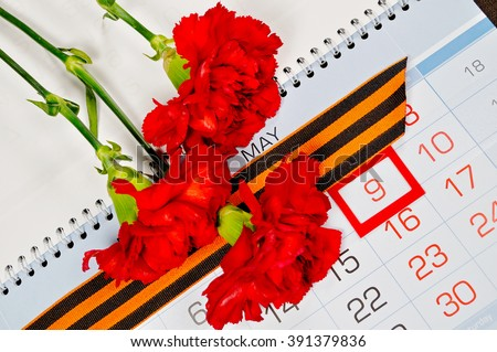 9 May concept.  St George ribbon and red carnations above the calendar with 9th May date - the day of victory in Great Patriotic War in Russia. 9 May postcard.  - stock photo