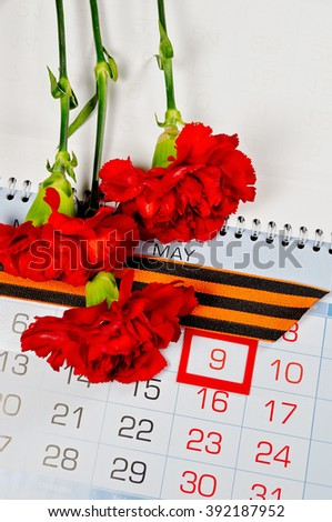 9 May concept. St George ribbon and red carnations above the calendar with 9th May date - the day of victory in Great Patriotic War in Russia. 9 May greeting card.  - stock photo