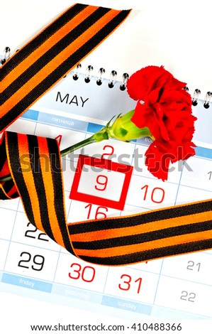 9 May concept. Victory Day card - bright red carnation wrapped with George ribbon lying on the calendar with framed 9 May date  - stock photo
