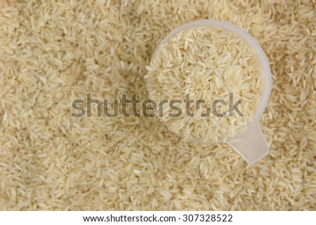 measuring cup filled with raw white rice with rice as background. basmati or jasmine rice used to prepare biriyani or pulav in India.uncooked long grain rice - stock photo