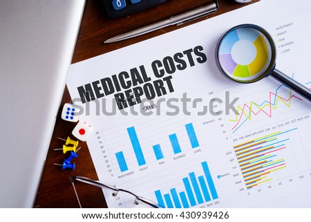 """Medical Costs Report"" text on paper sheet with magnifying glass on chart, dice, spectacles, pen, laptop and blue and yellow push pin on wooden table - business,banking, finance and investment concept - stock photo"