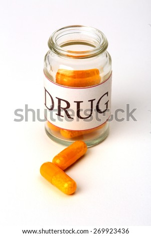 Medicine bottle with drugs close up over white - stock photo