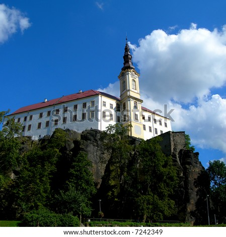 Medieval Czech castle standing on the rock with blue sky