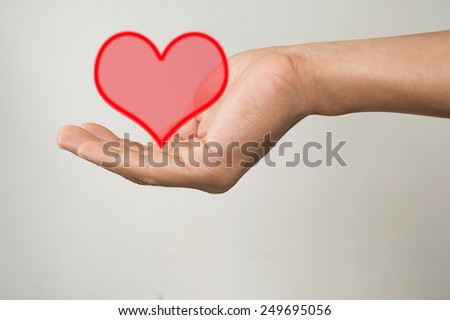 men hand holding heart isolated on gray