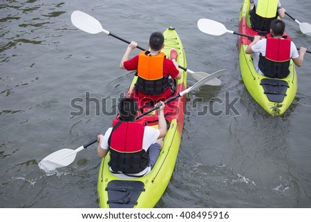 4 men paddle a kayak on the sea. Kayaking in sea - stock photo