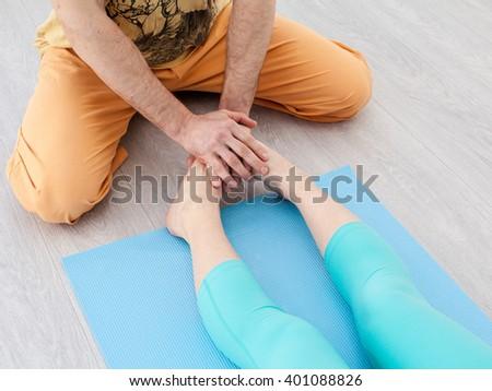 Men palm putting pressure on woman's legs - stock photo