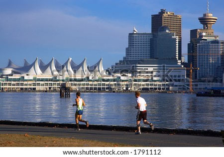 2 men running along Canada Place. - stock photo