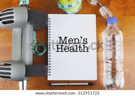 """Men's Health"" text on notebook with delicious green apple, measure tape, spectacle, a bottle of mineral water, and bodybuilding tools on wooden background - healthy, exercise and diet concept - stock photo"