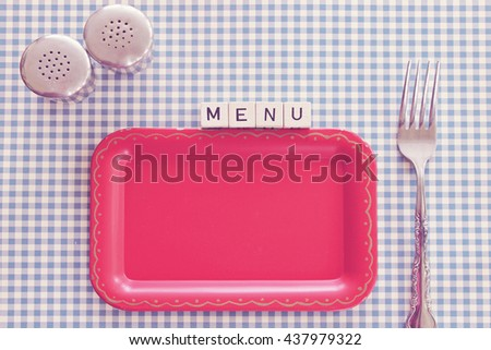 """MENU"" on dice overhead view checked tablecloth, vintage red tray, fork and salt and pepper"