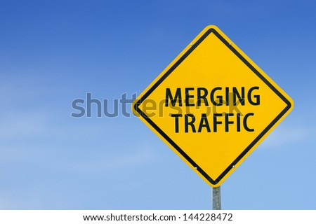 """MERGING TRAFFIC"" traffic sign with blue sky - stock photo"