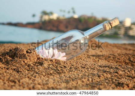 """message in a bottle"" in the sand  filled with plumeria flowers - stock photo"