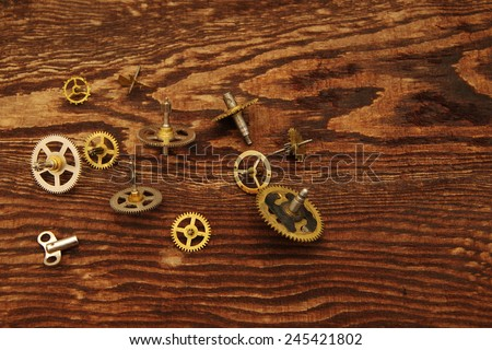 Metal details of the old broken hours on the made old brown wooden background - stock photo