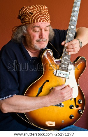 Middle aged guitarist with electric guitar - stock photo