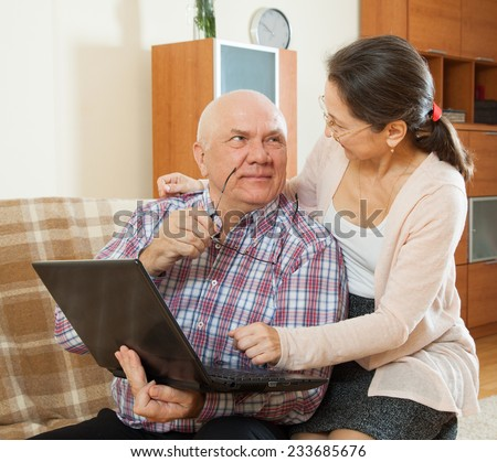 middle-aged man and woman sitting on  couch with  laptop