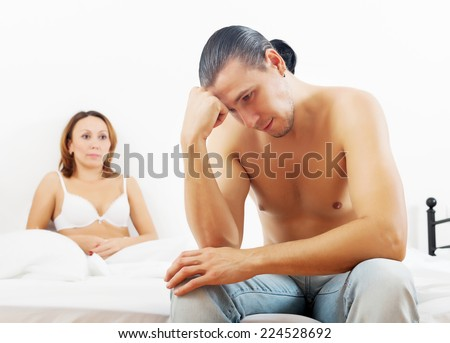 Middle-aged man has problem against his wife in bed - stock photo