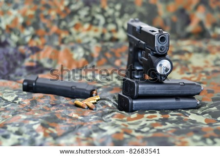 military sidearm pistol with a tactical laser/light-module on camouflage cover